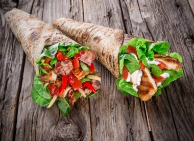 Chicken slices in a Tortilla Wrap on wood.