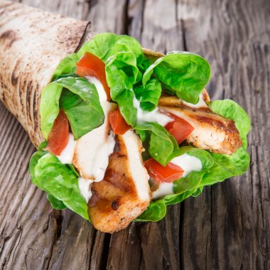 Chicken strips in a Tortilla Wrap with Lettuce on wood. stock vector