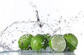 Fotografie Limes with water splash