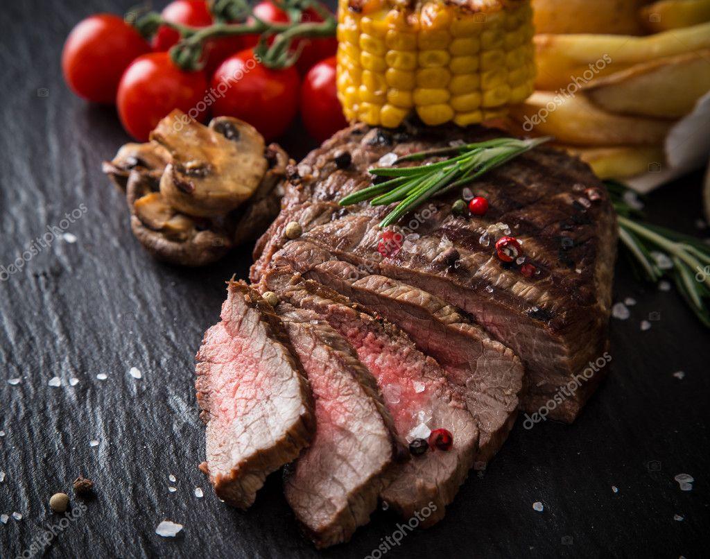Tasty beef steak on wooden table