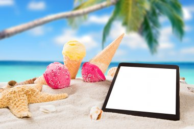 Tasty ice creams with tablet on the beach