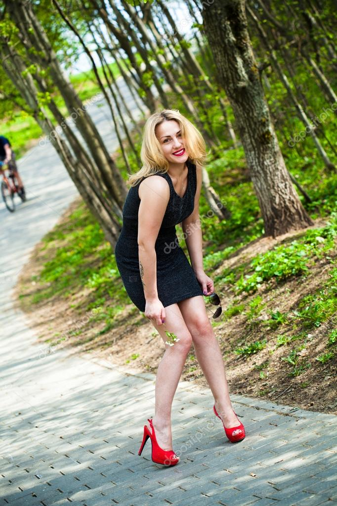 Portrait Of A Smiling Beautiful Girl In Nature In A Black Dress And