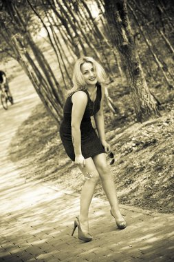 Portrait of a smiling beautiful girl in nature. sexy girl in a dress and shoes in the forest. Sepia toned photo