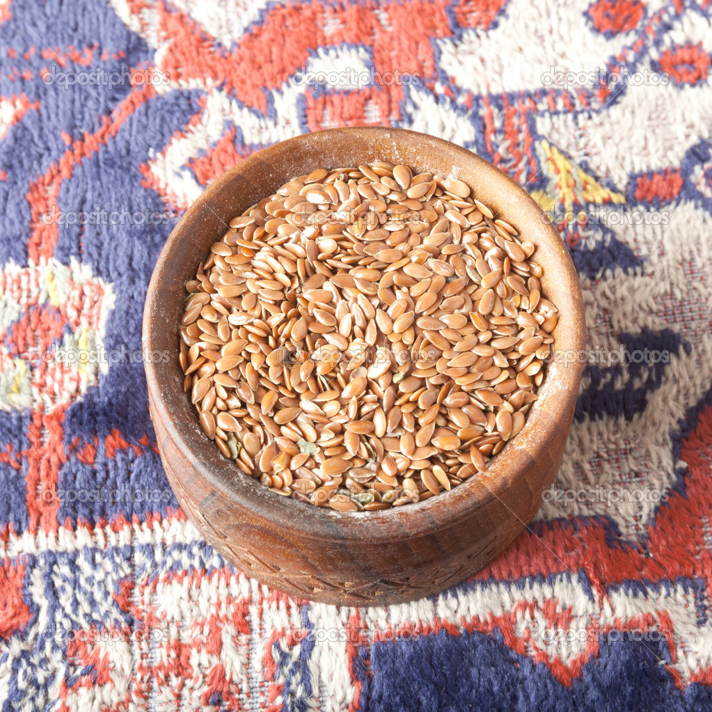 Flax seeds in a wooden bowl on the carpet with Armenian ornaments