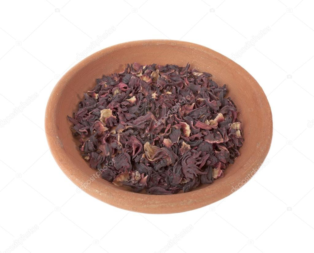 Dry leaves of hibiscus tea in clay bowl isolated on the white background