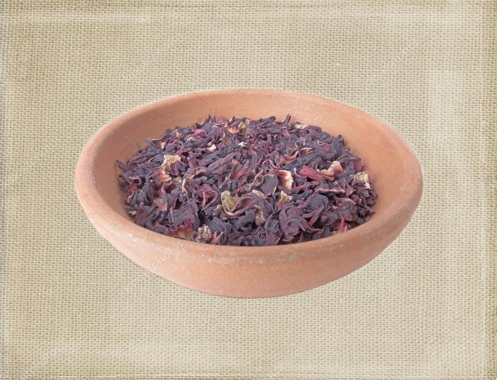 Dry leaves of hibiscus tea in clay bowl isolated over bagging background in old style