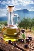Fotografia olive nere con bottiglia di olio su un tavolo di legno