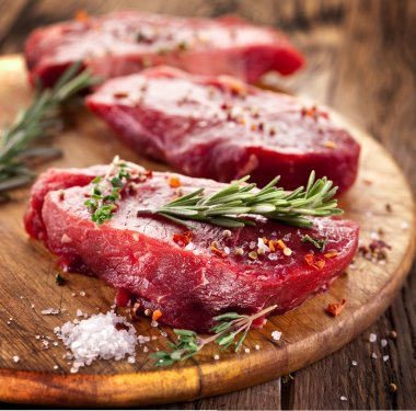 Raw beef steak on a dark wooden table. stock vector