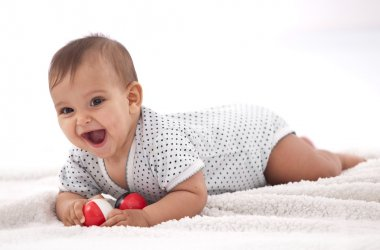 Laughing baby girl with small balls laying on the floor.