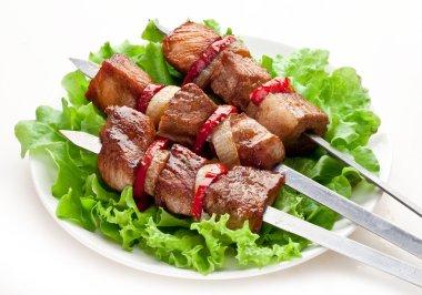 Grilled kebab (shashlik) on spits over lettuce leaves. stock vector