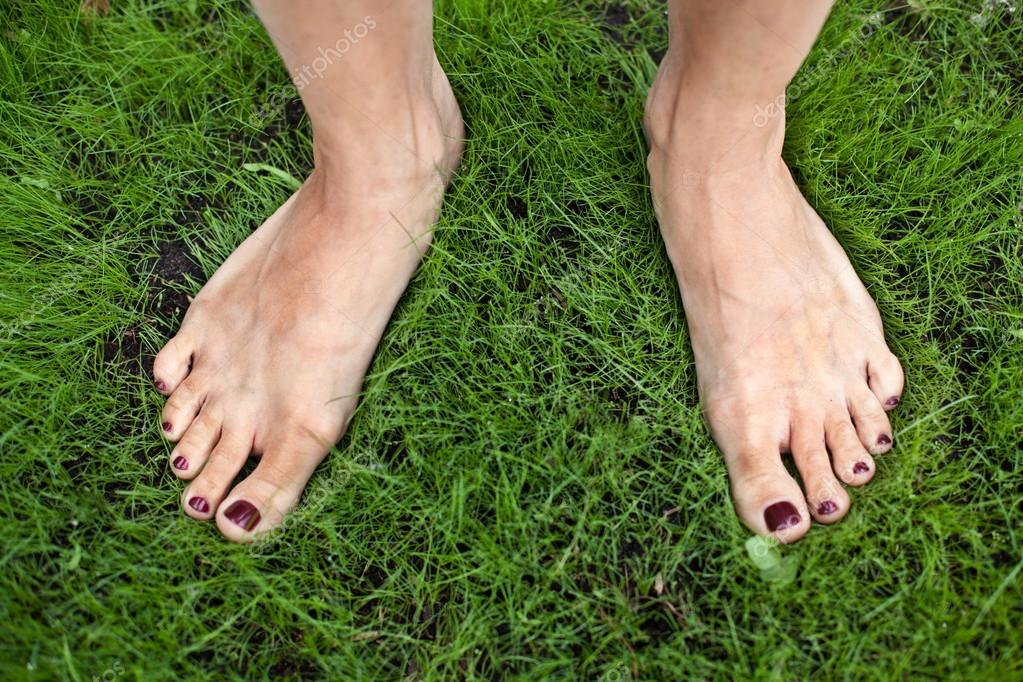 Woman feet on the grass.