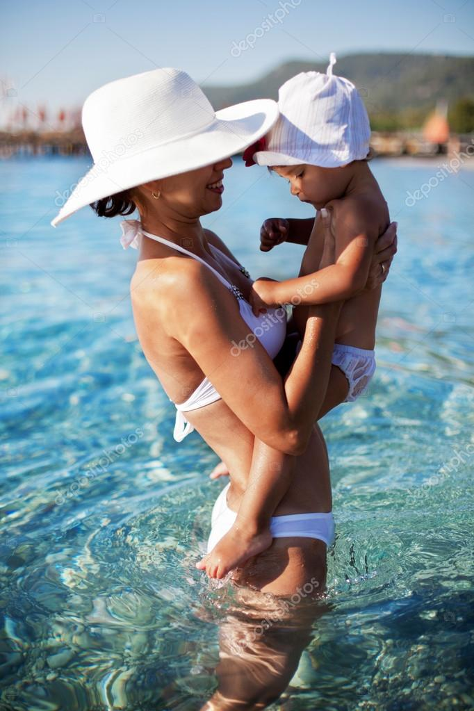 Mother and daughter staying in the sea water.