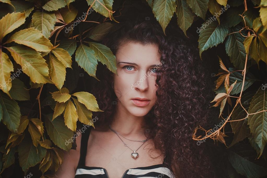 Fashion and beautiful young woman in a green wall of leaves