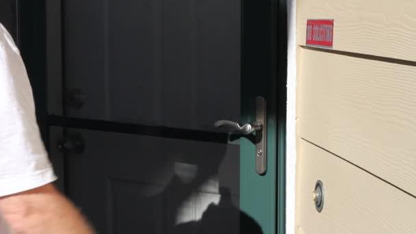 Mann klingelt an Haustür und klopft an