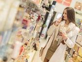 Fotografie Pretty young woman in perfumery