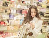 Fotografie hezká mladá žena v parfumerii