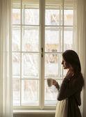 hübsche junge Frau am Fenster