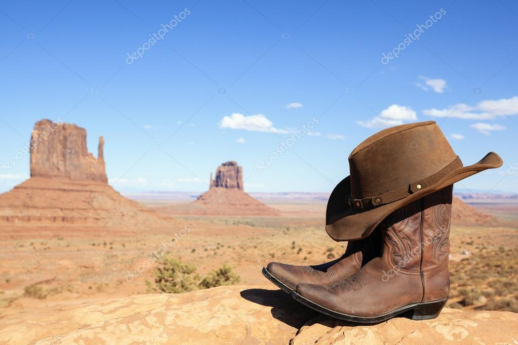 cowboy boots and hat in front of Monument Valley