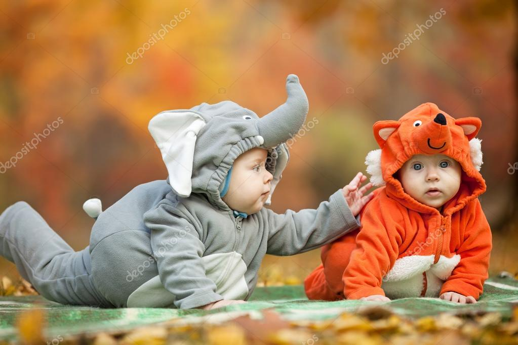 Two baby boys dressed in animal costumes in park