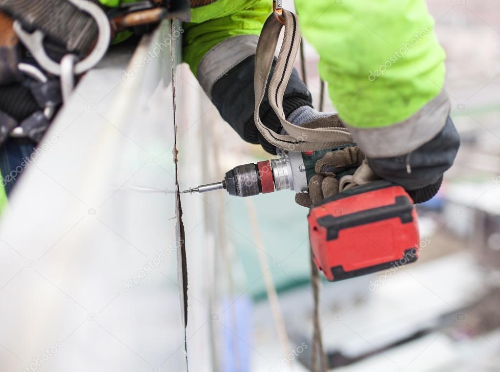 Closeup of industrial climber with screwdriver
