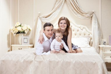 Young happy family with a baby on bed