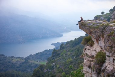 Young man sitting on edge of cliff