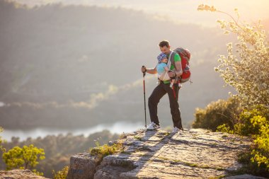 Hiker with baby relaxing standing on cliff