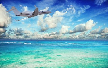 Private jet over the tropical sea