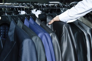Man choosing business jacket from the raw in the shop