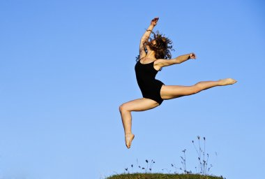 Yang ballet woman in training suit performs outdoor in sunset time