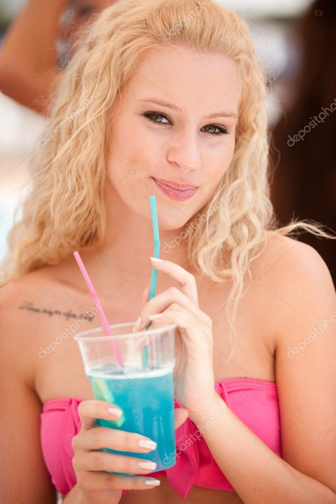jolie fille blonde boit cocktail bleu dans l 39 ombre sur un. Black Bedroom Furniture Sets. Home Design Ideas