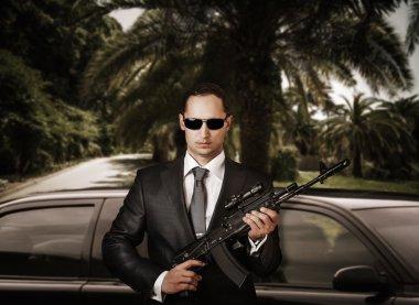 Confident bodyguard holding automatic.
