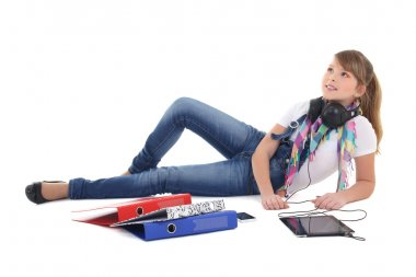 beautiful teenage girl lying and listening music with tablet pc