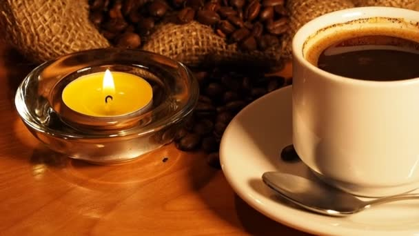 romantic background with candles, a cup of coffee and coffee beans in a bag