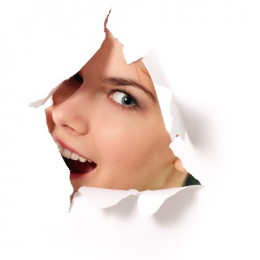 cheerful teen girl peeping surprised through hole in paper