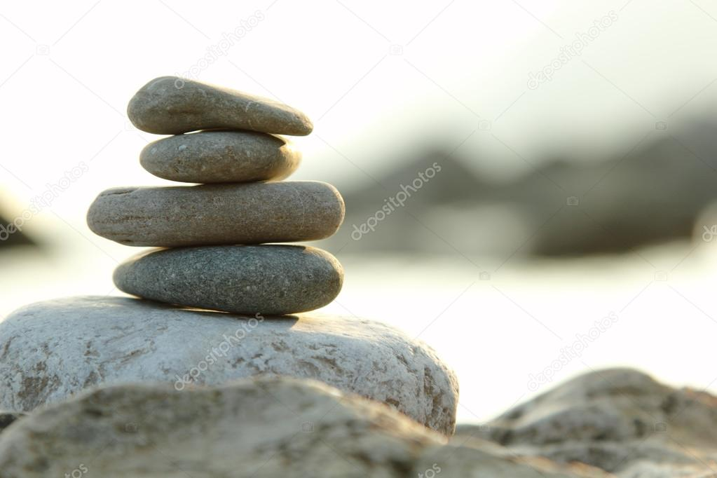 balanced stones over green nature background