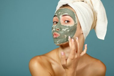 Teen girl applying facial clay mask