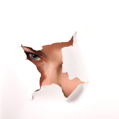 Girl peeping surprised through hole of paper