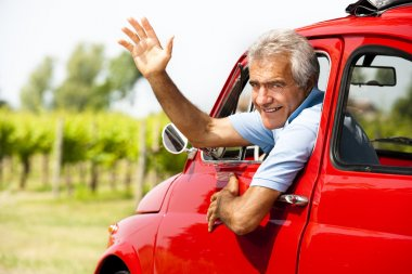 Senior man in vintage car