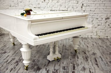 White piano with beautiful yellow rose