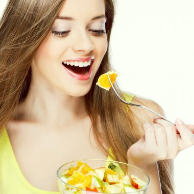 Portrait of a pretty young woman eating fruit salad