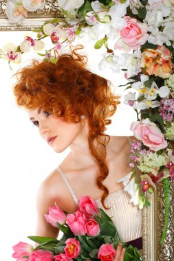 Beautiful redheaded girl with the bouquet of tulips, which stands in a gold frame, flowered, isolated on a white background