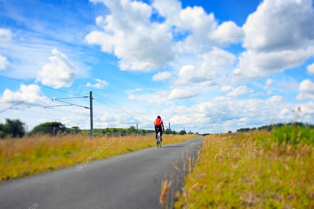 A cyclist on an empty rural road
