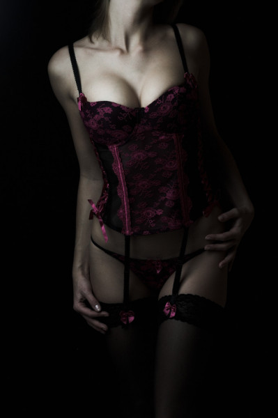 Sexy young girl with big breasts in pink black lingerie