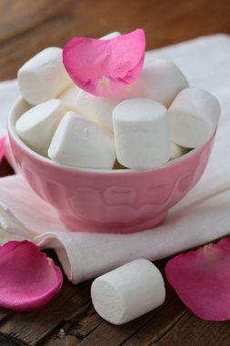 White marshmallows and pink rose petals on a wooden background