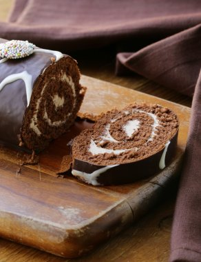 Chocolate cake roll with vanilla cream on a wooden board