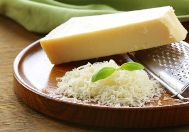 grated parmesan cheese and metal grater on wooden plate