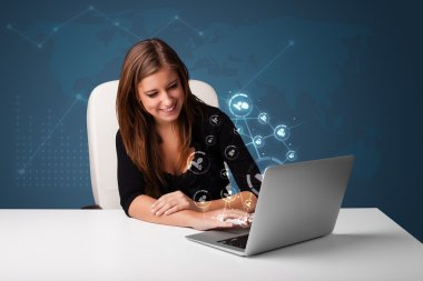 Young lady sitting at desk and typing on laptop with social netw