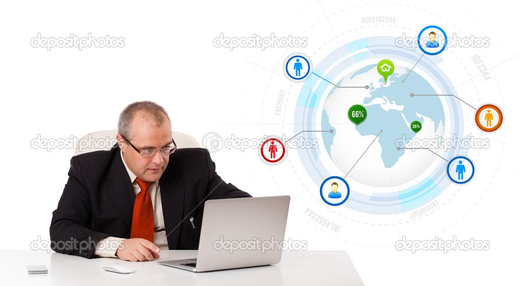Zakenman aan bureau zitten en op zoek laptop met globe en zo
