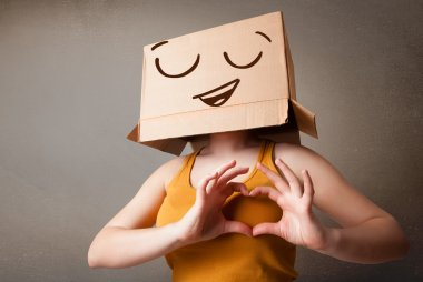 Young woman standing and gesturing with a cardboard box on her head with smiley face stock vector